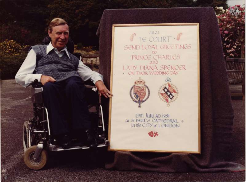 A man in a wheelchair sat next to a sign congratulating Prince Charles and Diana on their wedding