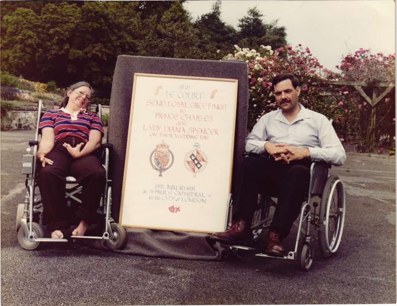 A man and a woman in wheelchairs sat next to a sign for Prince Charles and Diana's wedding
