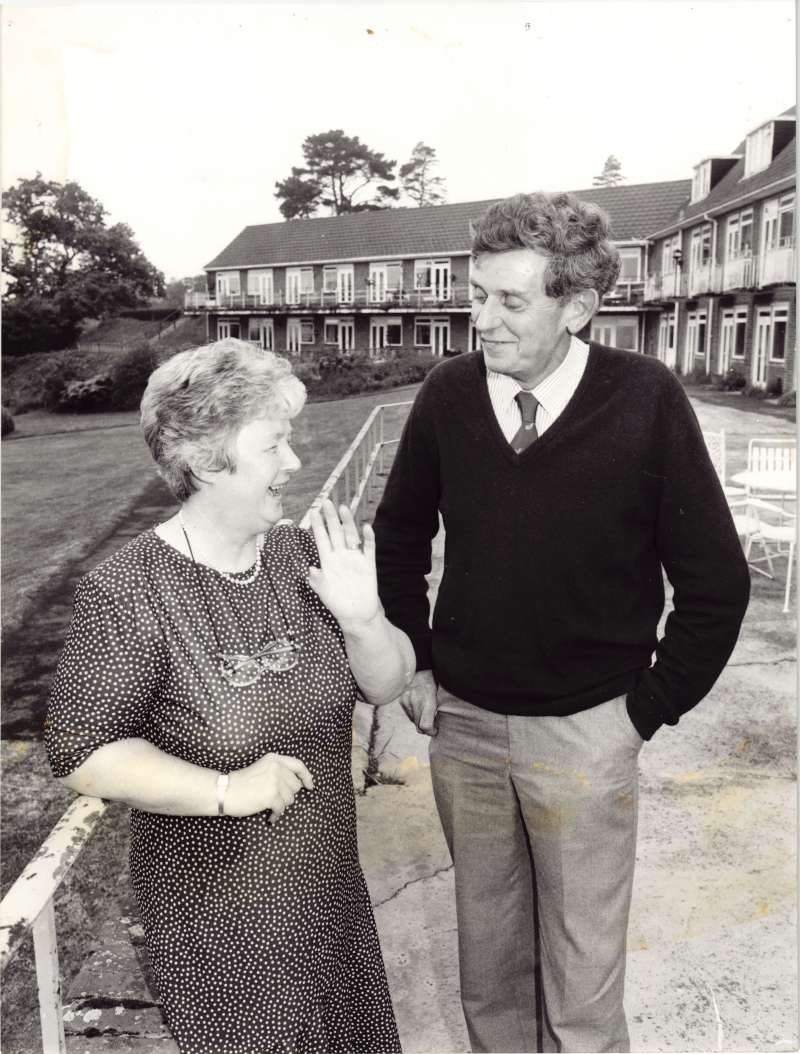 A woman in a black and white spotty dress talking to a man in a dark jumper on the terrace outside a brick building