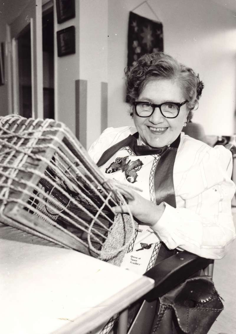 A woman in a wheelchair wearing an apron, weaving a basket on her lap