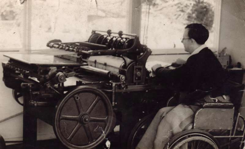 A young man in a wheelchair operating a large printing press machine