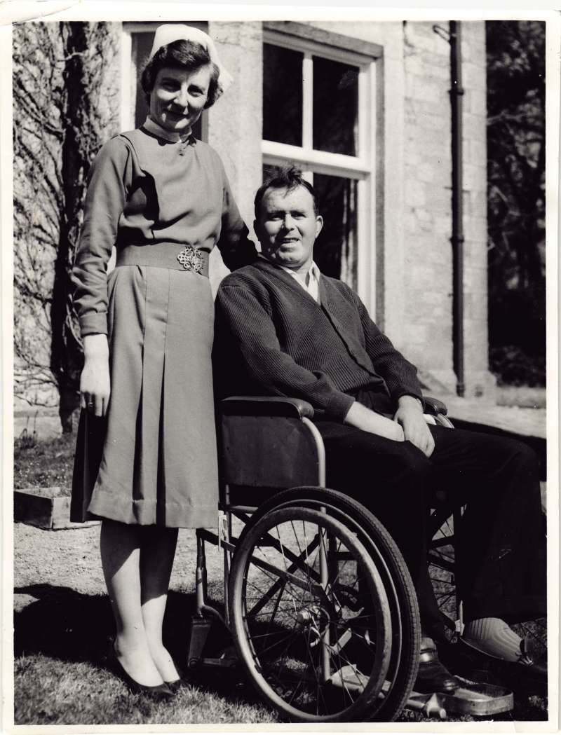 A woman in a nurse uniform standing next to a man in a wheelchair outside at Le Court