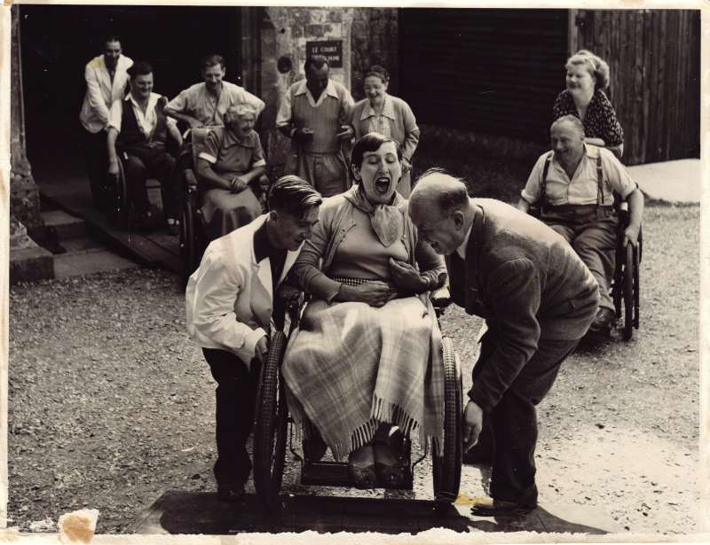 A woman in a wheelchair being pushed up a ramp whilst others in wheelchairs watch from behind