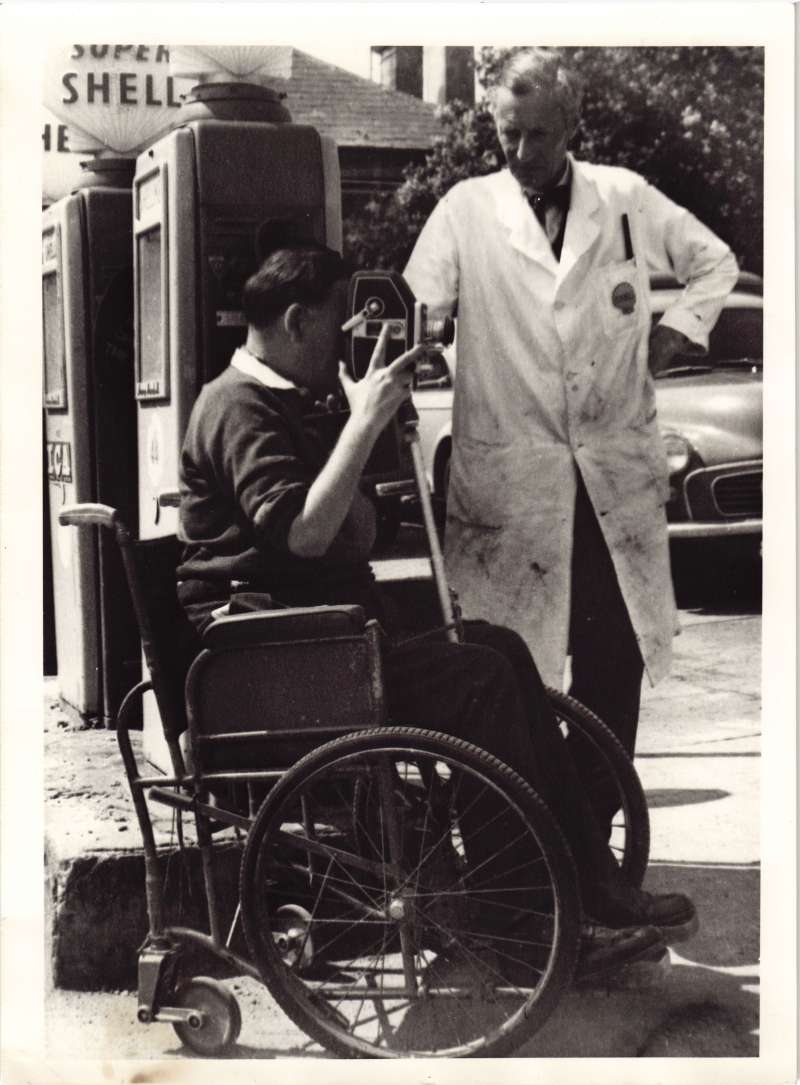 A man in a wheelchair using a camera tripod set in his lap, with a man in white overalls watching on