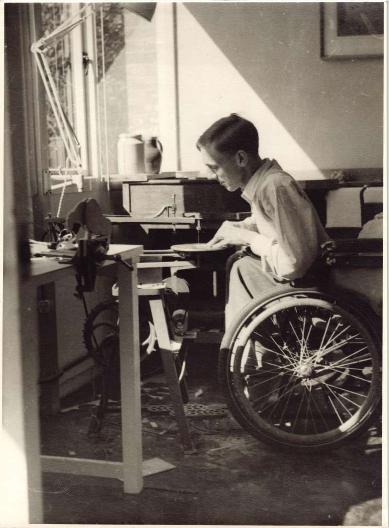 A young man in a wheelchair at a workbench inside a workshop