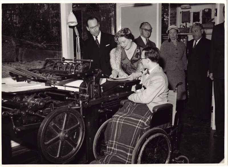 HM The Queen Mother being shown the printing press used to produce the Cheshire Smile with Leonard Cheshire nearby
