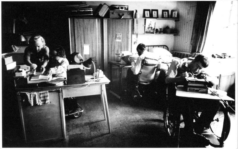 3 men at desks in a bedroom working on typewriters, with a lady helping one of them
