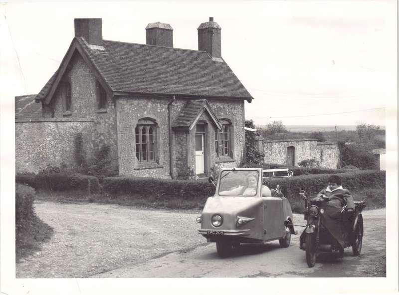 A woman in a small 3-wheeled car and a man in a 3-wheeled motorcycle on a country lane outside a cottage