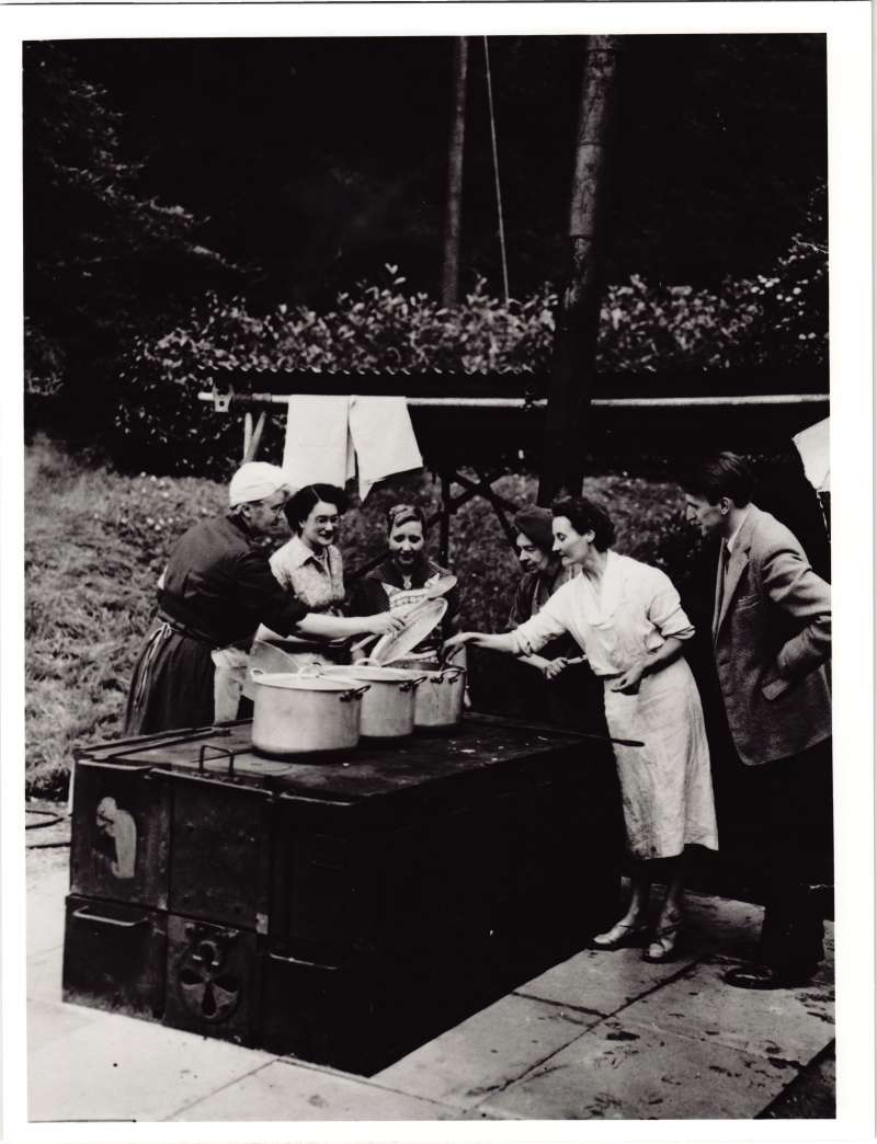 Several women cooking in an outside kitchen