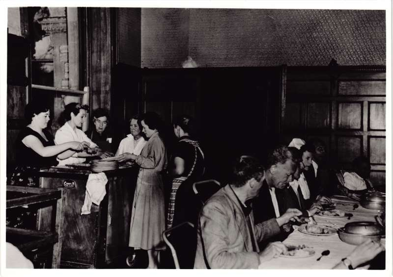 Several people eating at a long table, with a group of people behind at a large serving trolley dishing out food