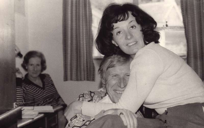 A smiling older man being hugged by a younger woman, with a woman looking on in the background