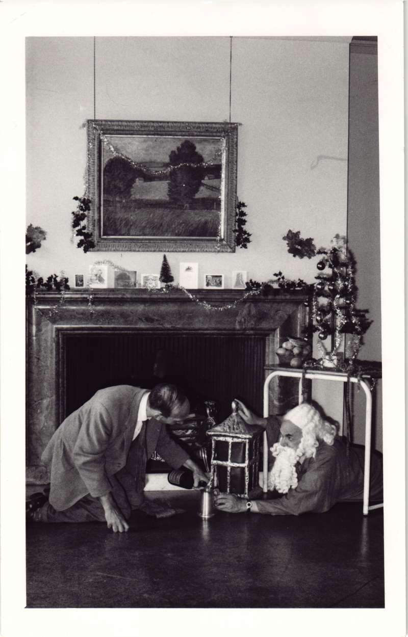 A man kneeling in front of a fireplace pouring something into a glass for a man dressed as Father Christmas who is lying on the floor