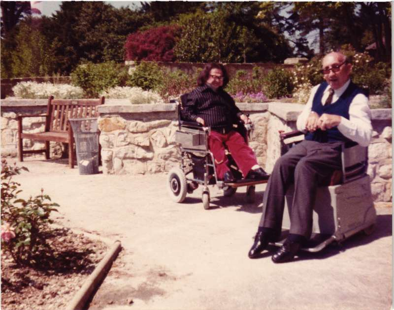 Two men in wheelchairs in the garden in the sunshine
