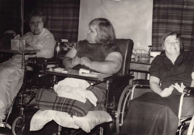 Three women in wheelchairs sat inside, one with cigarettes on her lap tray