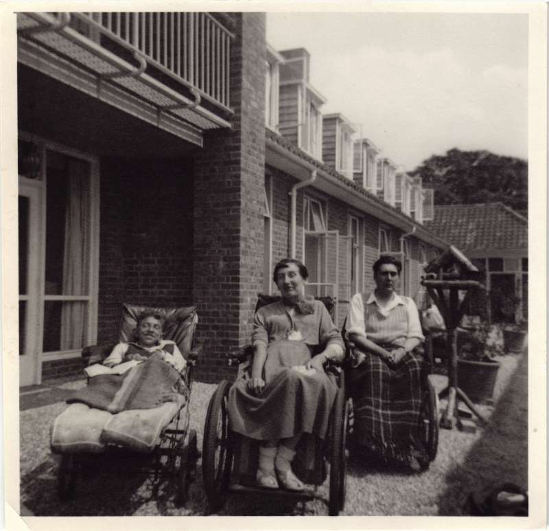 Two young men and a woman in wheelchairs sat in front of a building smiling at the camera