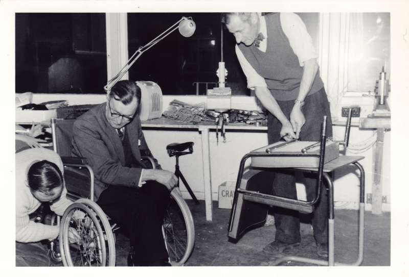 A man sat in a wheelchair whilst another man adjusts the wheel mechanism. Another man altering a wheelchair seat