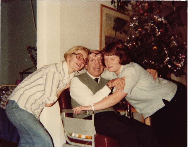A man in a wheelchair in front of a decorated Christmas tree being hugged by two young women