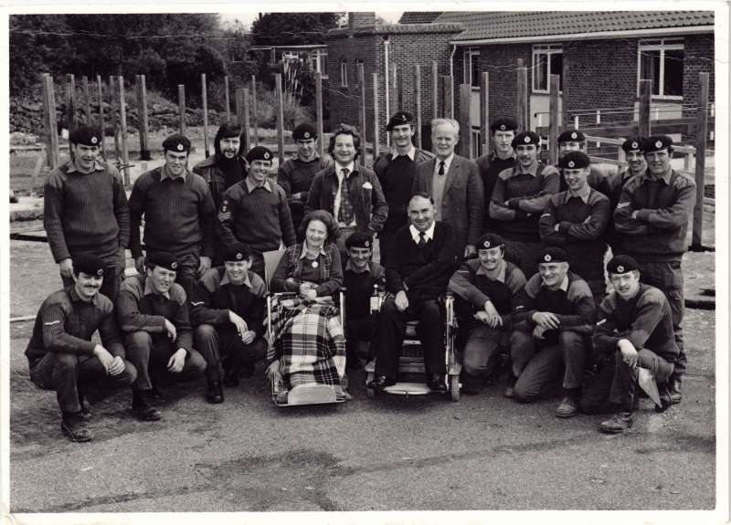 Posed group of soldiers in uniform in gardens with a man and a woman in wheelchairs