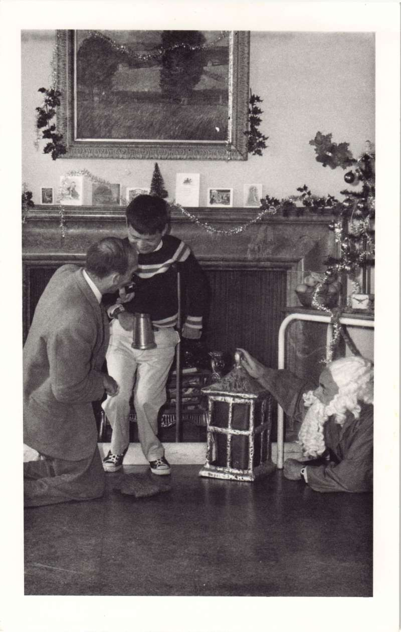 A man kneeling and a man with crutches standing in front of a fireplace, with Father Christmas crawling out from under a table