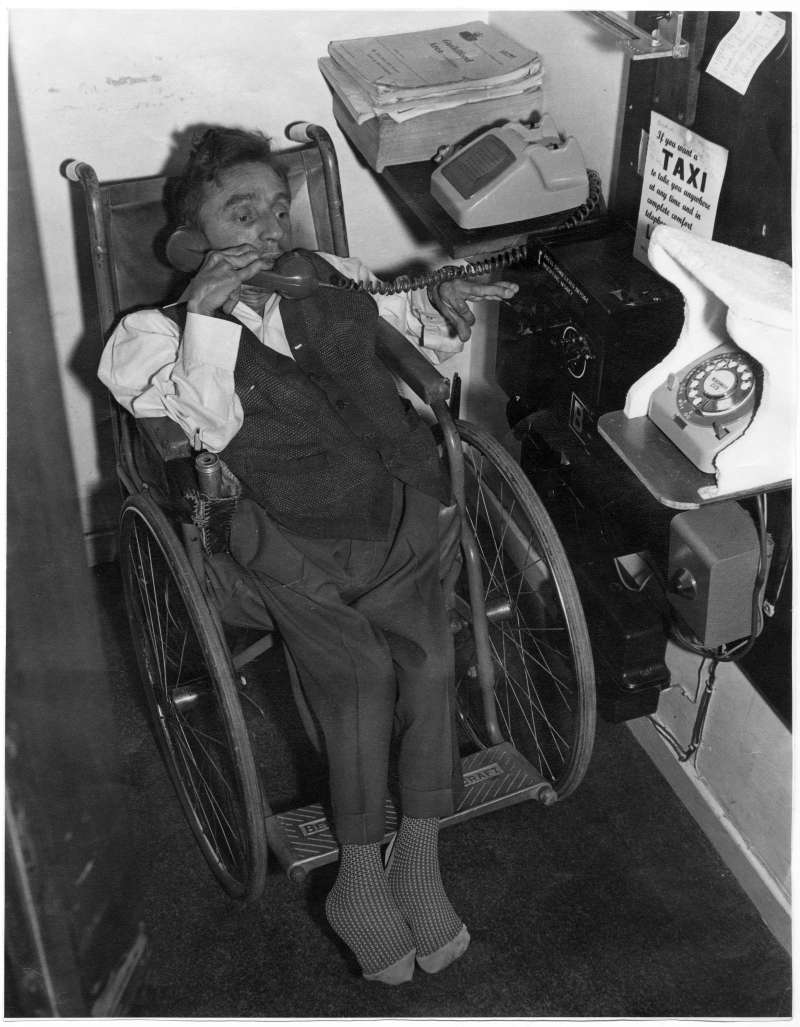 A man in a wheelchair using a specially adapted telephone