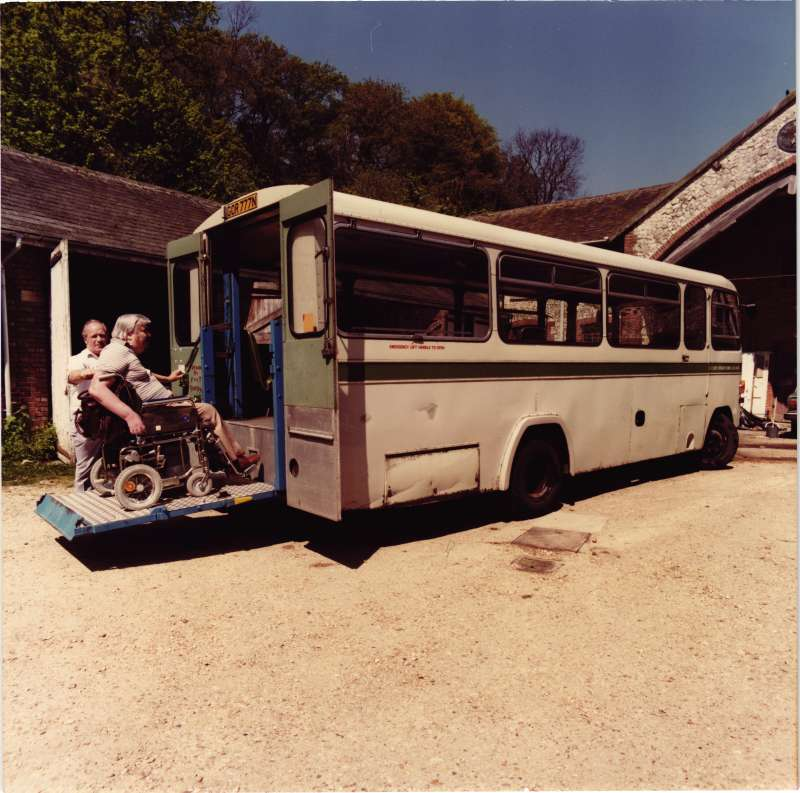 A man in a wheelchair using a rear moveable ramp to access a minibus, assisted by another man