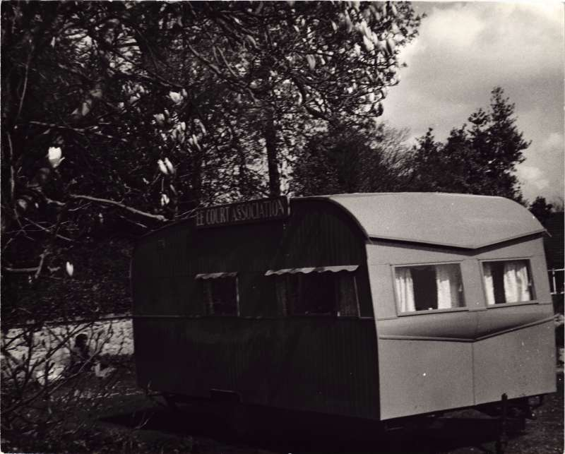 An old caravan with the words 'Le Court Association' attached to it standing in amongst trees