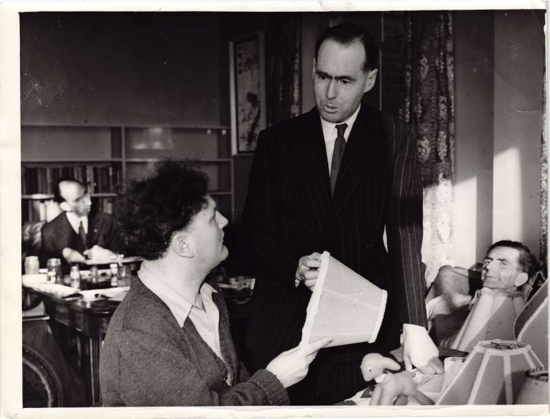 Leonard Cheshire talking to a man in a wheelchair holding a lampshade, with two other men in the background