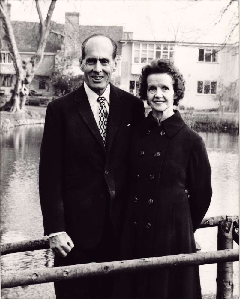 Leonard and Sue standing on a bridge over a pond, with a house in the background