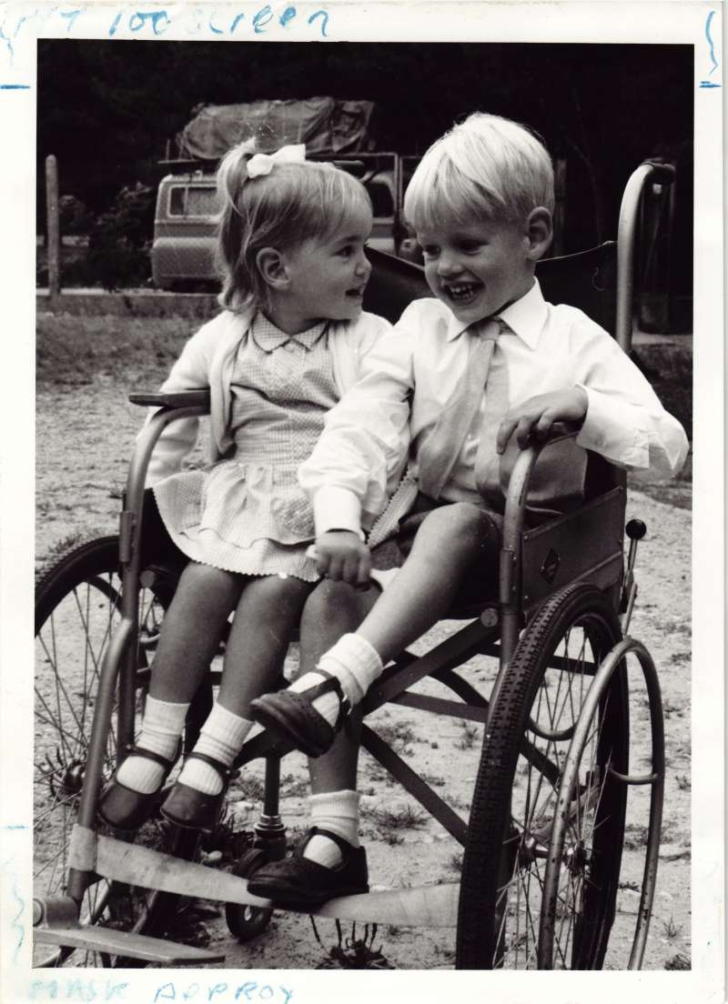 A young girl and a young boy laughing, sat together in an adult's wheelchair