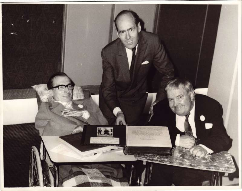 Leonard Cheshire standing between two men in wheelchairs holding a presentation book