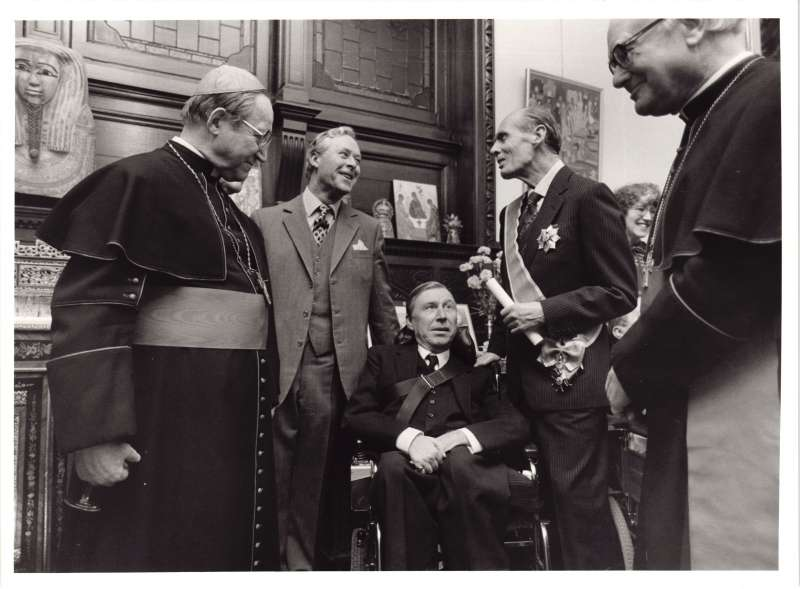 Leonard Cheshire talking with Cardinals in ceremonial clothing, with a man in a wheelchair in the middle