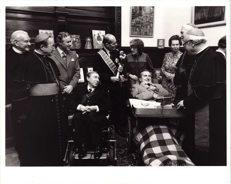 Leonard Cheshire talking with Cardinals in ceremonial clothing, with 2 men in wheelchairs in the middle