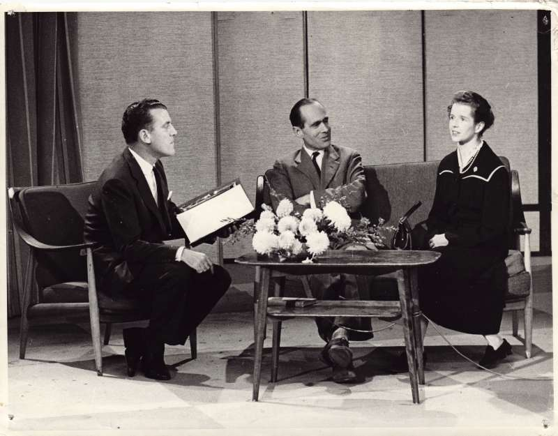 Leonard and Sue sat on a sofa on a television set being interview by another man