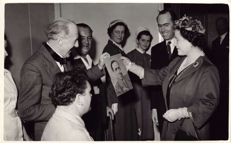 The Queen Mother admires a painting of Leonard Cheshire