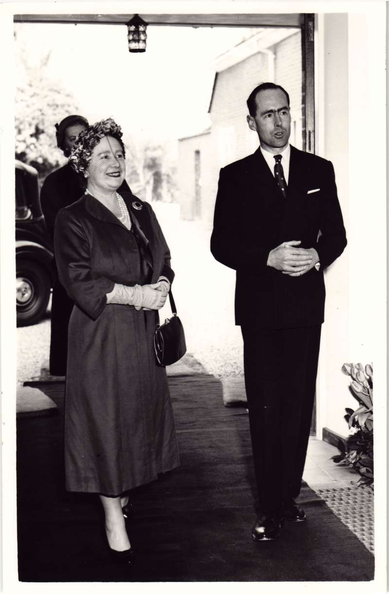 HM The Queen Mother and Leonard Cheshire walking through a doorway into the new Le Court house