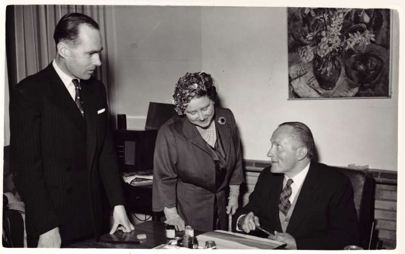 Leonard Cheshire and HM the Queen Mother talking to a man painting a picture at a table