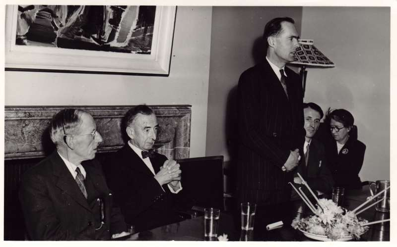 Leonard Cheshire giving a speech at a dining table with other guests