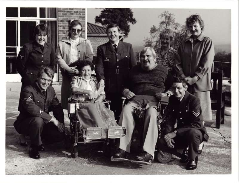 A posed group of men and women in uniform with a man and woman in wheelchairs