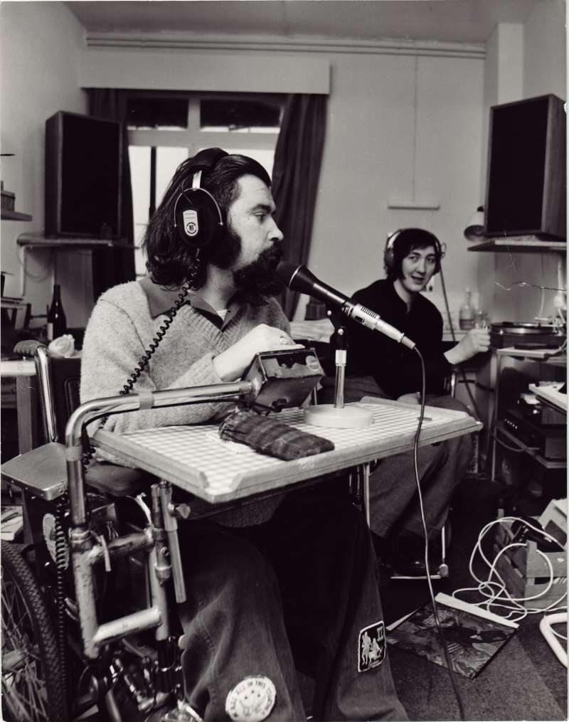 A man in a wheelchair with headphones and microphone in a home-based recording studio, with another person wearing headphones in the background