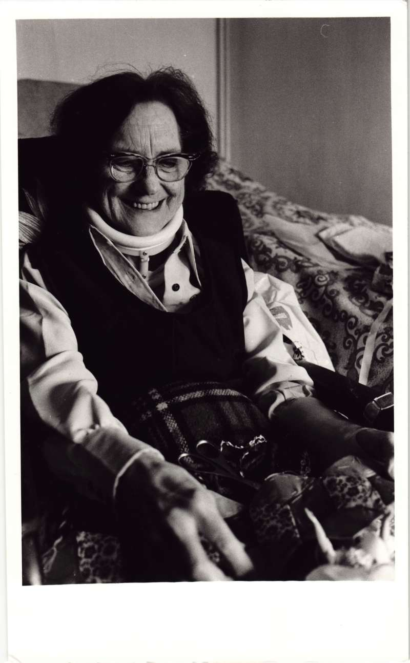 An older woman in a bedroom smiling at needlework accessories in her lap