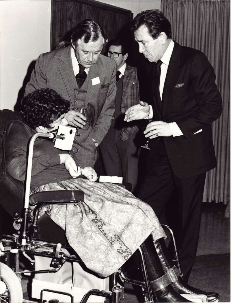A woman in a wheelchair talking with two men in suits holding wine glasses
