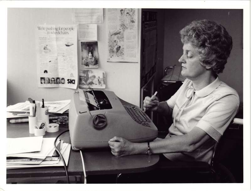 A woman in a wheelchair at a desk using a pen to hit the keys on a typewriter