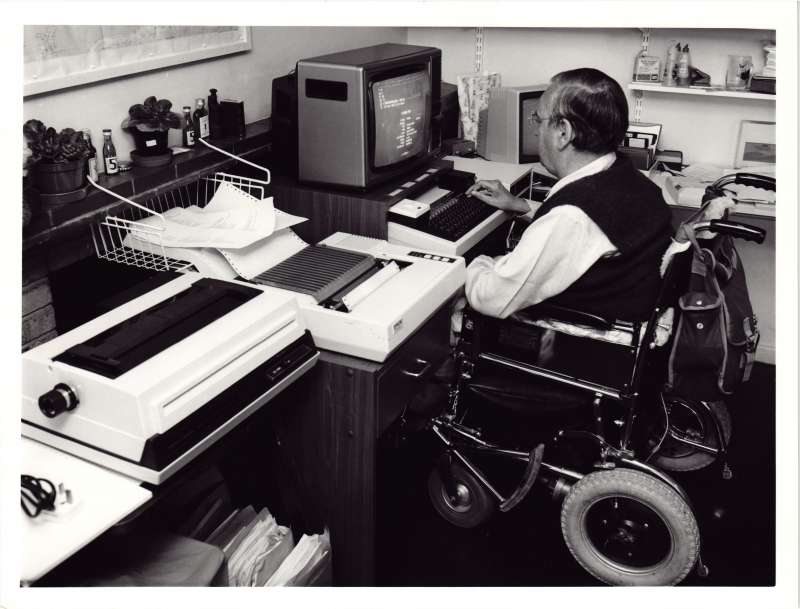 A man in a wheelchair sat at a desk in front of an early word processor and printer