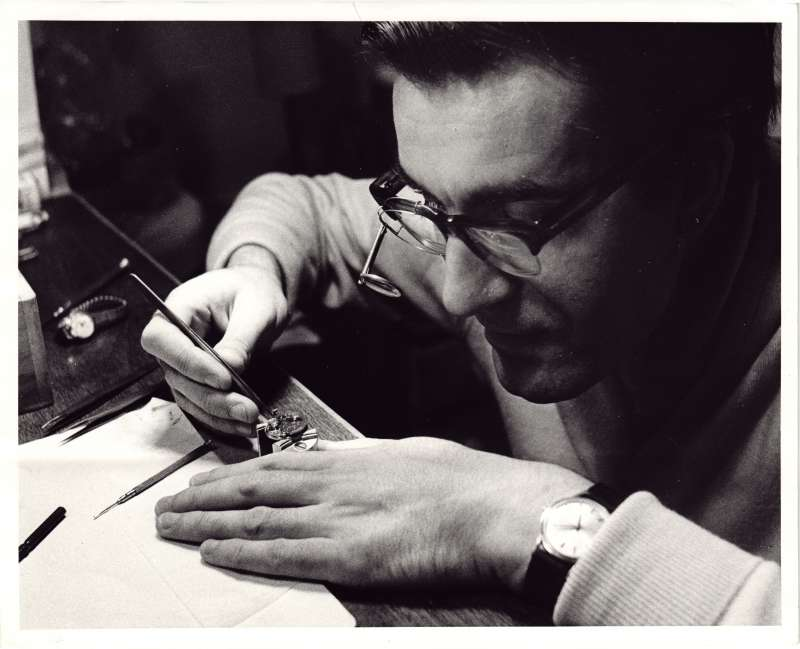 A close up of a man using specialist tools to mend a watch