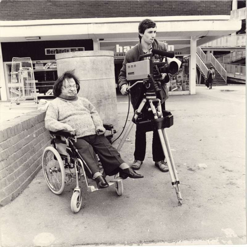 A man in a wheelchair with windswept hair and a younger man filming with a video camera in a town centre