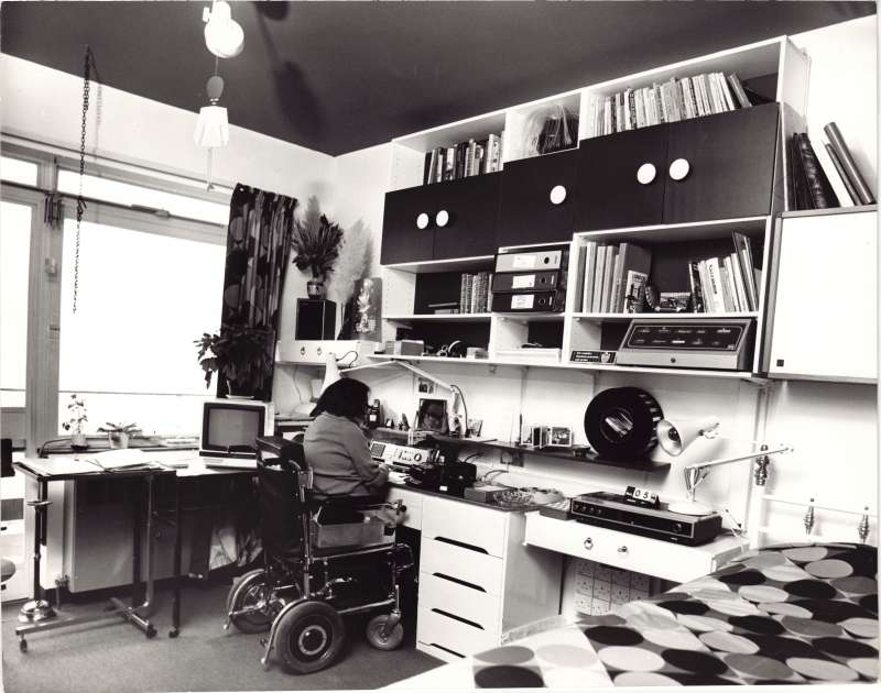 A man in a wheelchair with his back to the camera sat at a desk with various film and recording equipment around the room