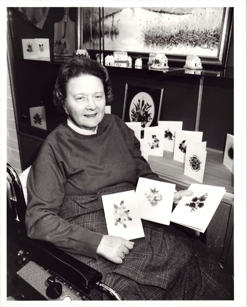 An older woman in a wheelchair displaying several handmade cards of flowers