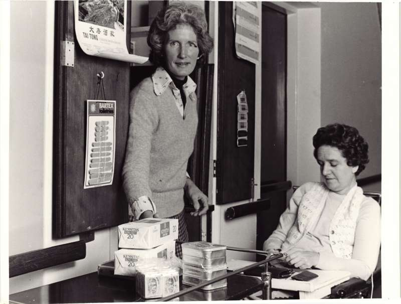 A woman standing in a doorway with another woman with a purse in her lap in front of several boxes of cigarettes