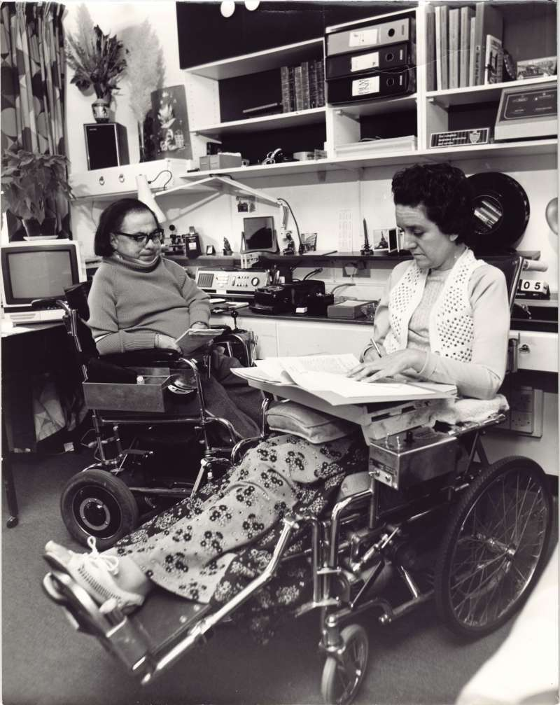 A man and a woman in wheelchairs both working on documents on their laps