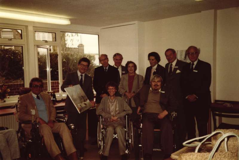 A group of people, some in wheelchairs in a new workshop, some holding painted pictures